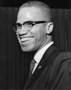 a black and white image of Malcolm X