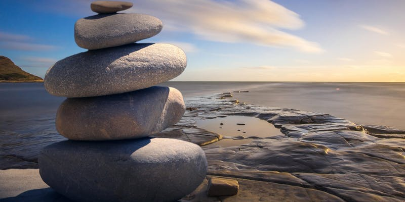 a stack of round rocks at the seaside