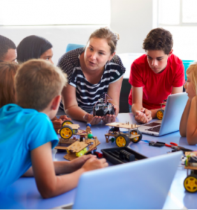 Image of teacher surrounded by students at a desk, talking