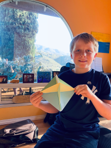 Picture of boy holding up a piece of origami that he created for Project VisMO.