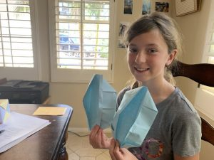 Picture of girl holding up a piece of origami that she created for Project VisMO.