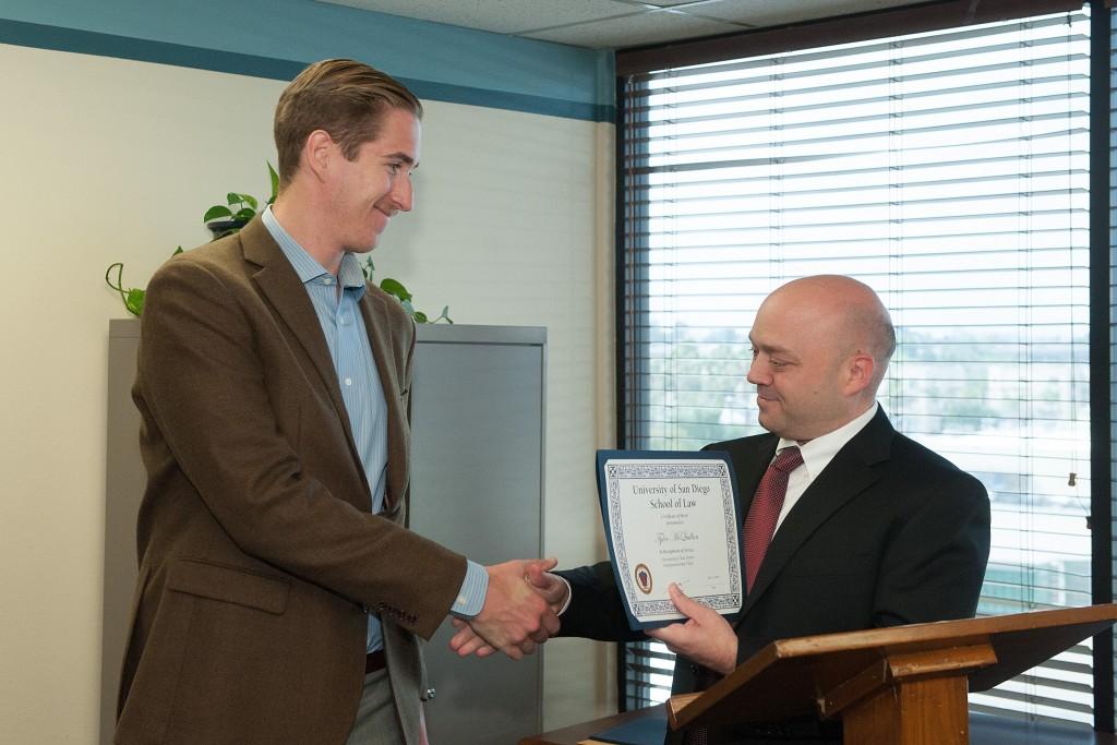 Legal intern Tyler McQuillan receiving the Entrepreneurship Award with Supervising Attorney Sebastian Lucier.