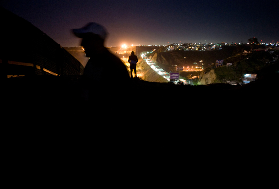 Two men look over the U.S.-Mexico border wall, left, for U.S. Border Patrol agents on a hilltop in Tijuana, Mexico 2013. Photo - David Maung, 2013