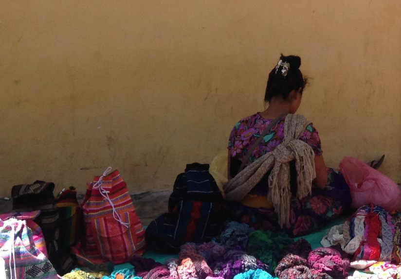 A woman selling crafts outside the cathedral in San Cristóbal. Photo: Pablo de Llano