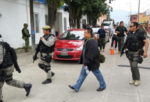 Pedro Tamayo Rosas returns from Oaxaca, guarded by police. Photo from El Piñero de la Cuenca