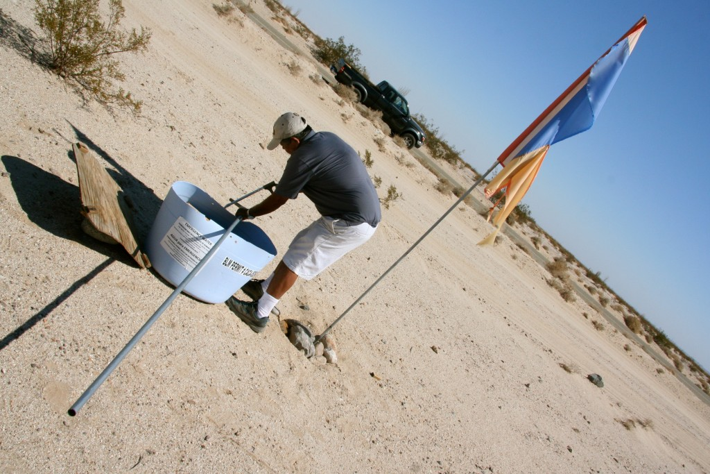 Francisco, a long-time volunteer with Water Station, had been placing water in remote desert areas north of Highway 8 with his sons prior to joining Water Station. Here he saws a metal pole that will raise the Water Station flag 20 feet into the air. Photo by Pedro Rios.