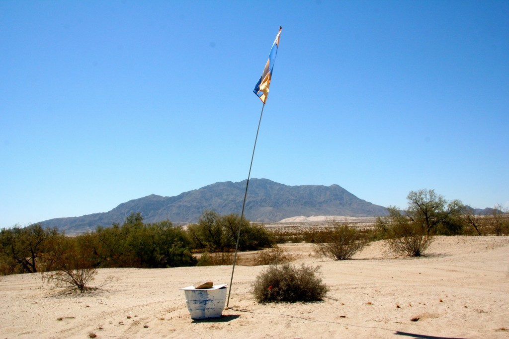 A water station along State Route 98 with the backdrop of the famous El Centinela (The Sentinel) summit, at times visible from the Salton Sea. Every year volunteers place an average of about 50 water stations along this route, most of which runs parallel to the U.S.-Mexico border. Photo by Pedro Rios.