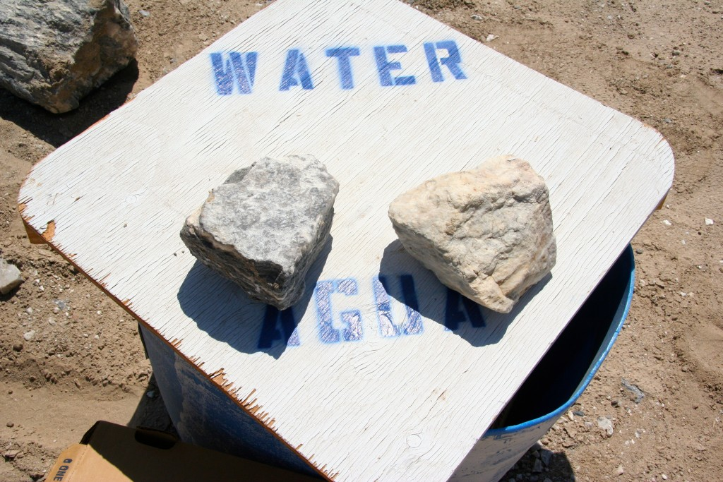 A flat wooden cover is labeled with water, agua. It is kept down by large rocks that are easily removable should someone need access to the gallons of water kept inside the barrel. Throughout the years, the water has saved the lives of migrants, hikers, and dirt bike aficionados lost in the desert. Photo by Pedro Rios.