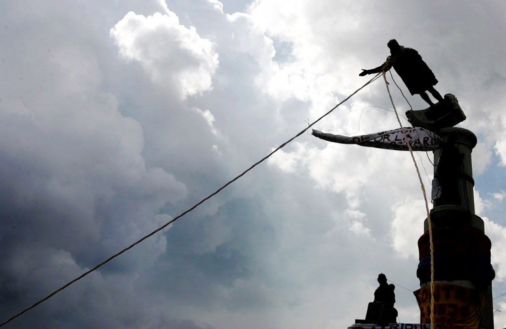 "12 Oct 2004, CARACAS, Venezuela --- Venezuelan demonstrators use ropes to topple a Christopher Columbus statue in Caracas, October 12, 2004.  Demonstrators protested during Columbus Day, a date which Venezuelan President Hugo Chavez has christened as the ""Day of Indian Resistance"" to commemorate the Indian people who fought the Spanish colonizers after the discovery of the continent by Christopher Columbus. --- Image by © JORGE SILVA/Reuters/Corbis"