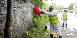 USD Professor Eric Pierson joins students in cleaning graffiti off a bridge in London during a study-abroad trip.