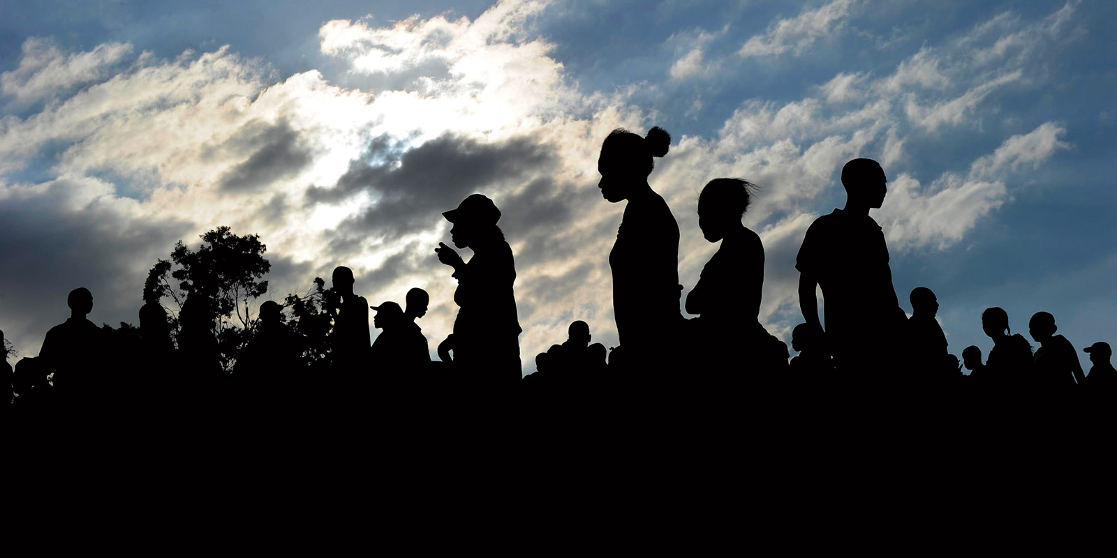 silhouettes of Haitians against a cloudy sky