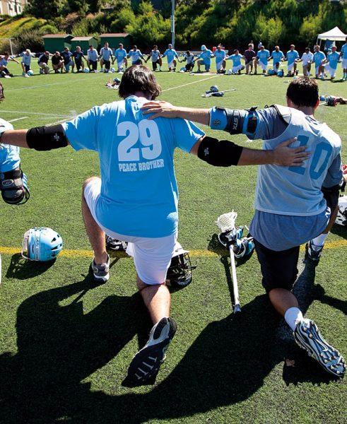 USD Men's Alumni Lacrosse Squad gather in a circle to pay tribute to late friend Dave Wodynski '92
