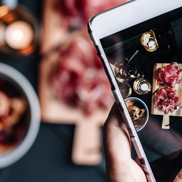 Photo of hand holding phone taking photo of food
