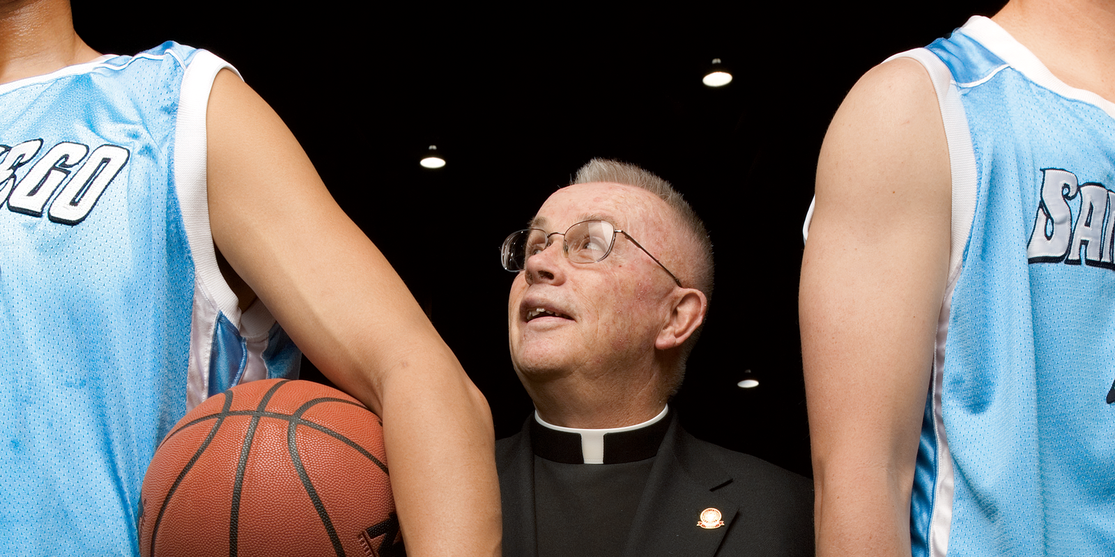 Father Owen Mullen flanked by two basketball players.