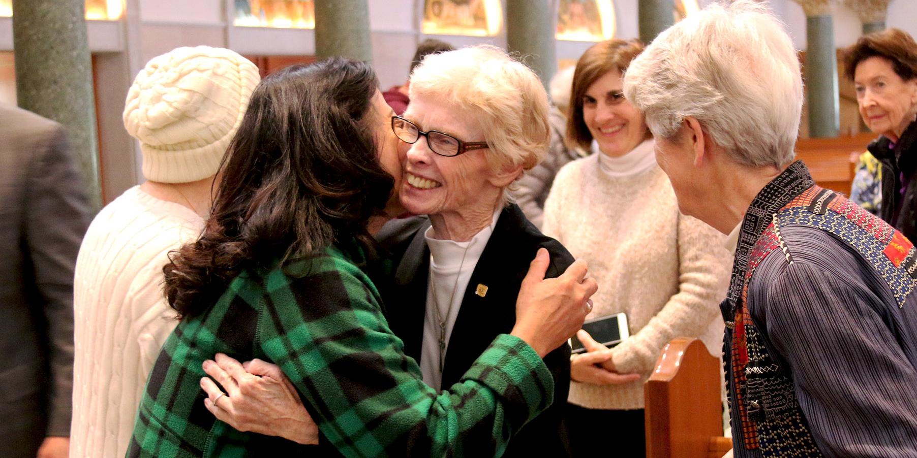 Sister Betsy Walsh gives a parishoner a farewell hug
