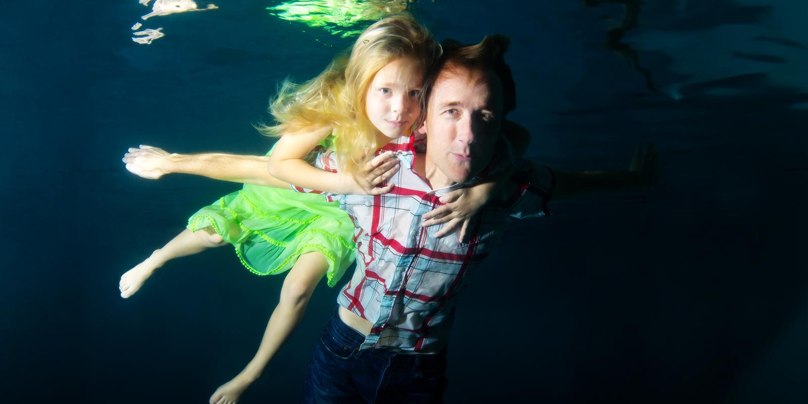USD alumnus Steve Melen floats underwater alongside his daughter, Ava.