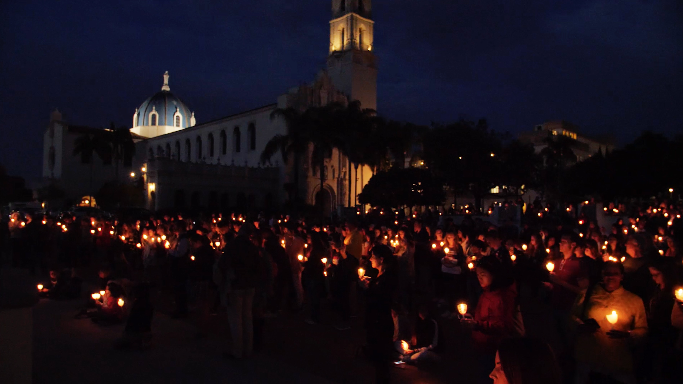 The Immaculata at night with students holding candles.