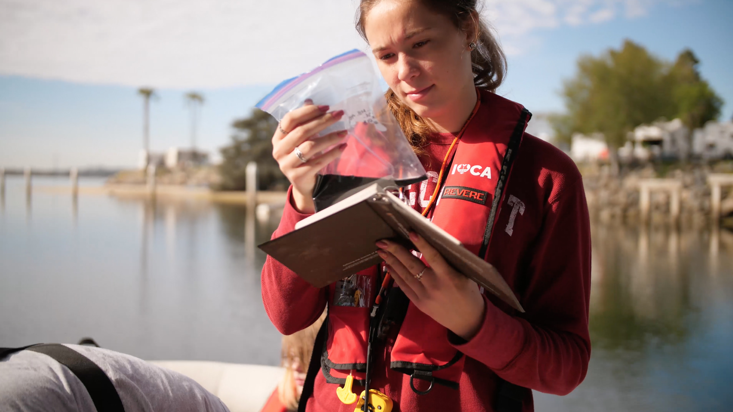 A female student examines a soil sample on a boat in Mission Bay