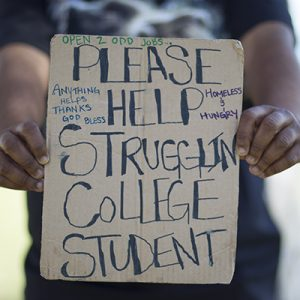 "Hands holding ""please help struggling college student"" sign"