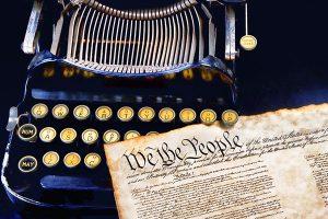 "Vintage typewriter next to document beginning ""we the people"""