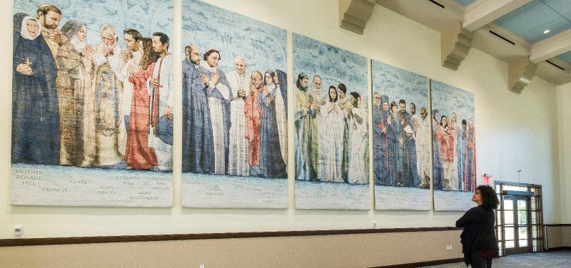 A person stands in front of the new tapestries that adorn the hall at the University of San Diego's new Ministry Center.