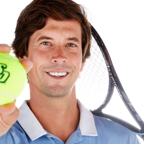 USD Men's Tennis Coach Ryan Keckley holds a tennis racket and ball