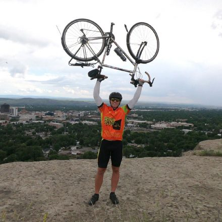 USD alumnus Payton Stanaway lifts his bicycle over his head in triumph