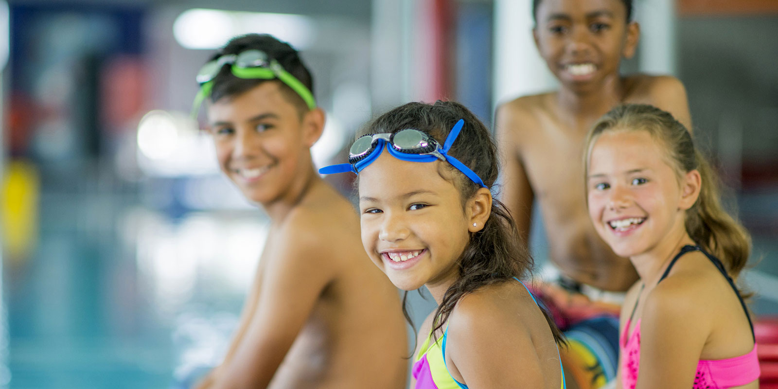 Smiling children sit by the edge of a swimming pool