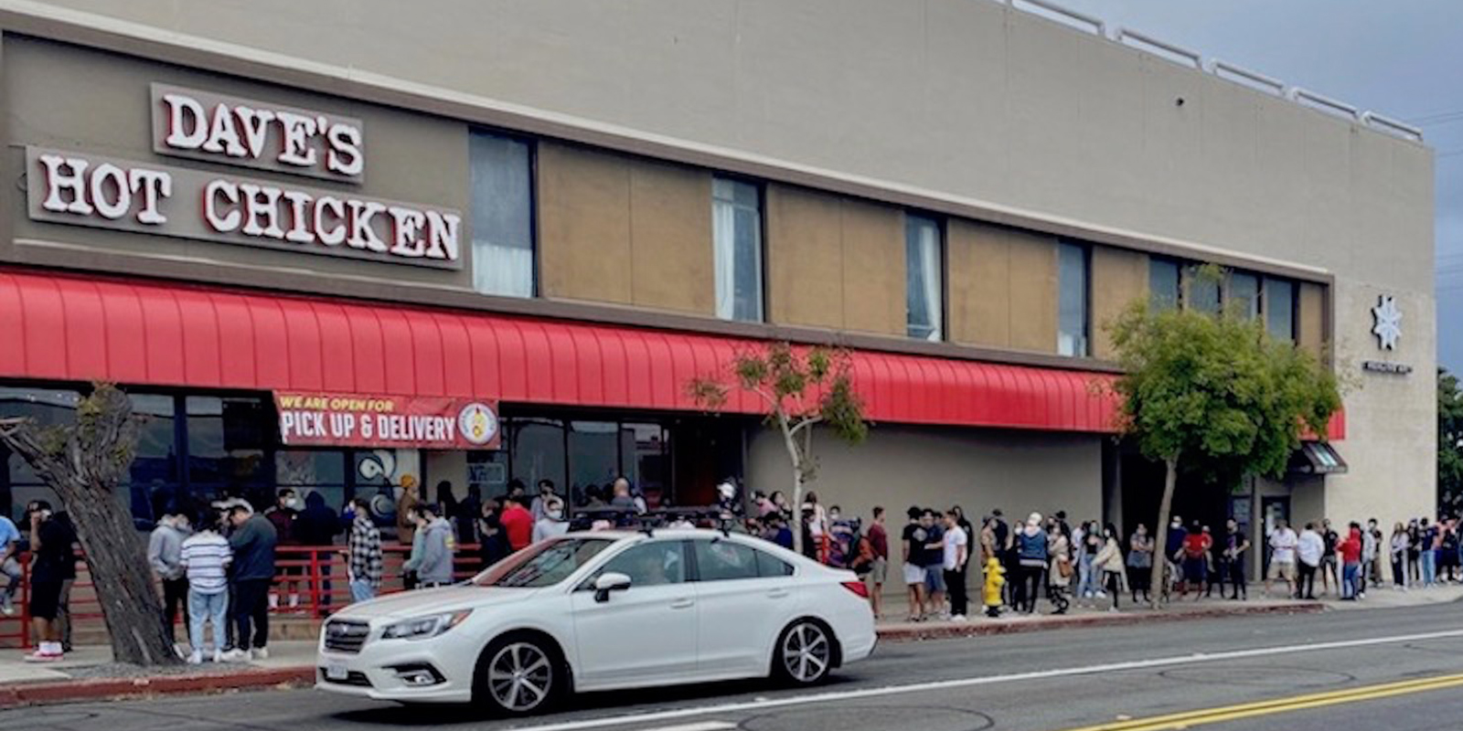 People waiting in line outside of Dave's Hot Chicken franchise