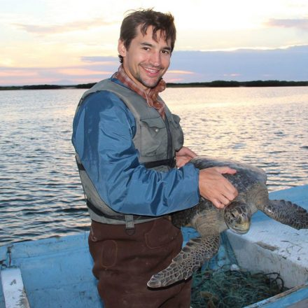 USD alumnus Travis Kemnitz '02 (BA), holding a turtle on a boat