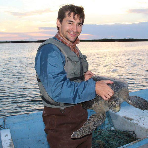 USD alumnus Travis Kemnitz '02 (BA), holding a turtle on a boat