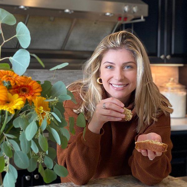 USD student Chloe Zakhour '20 (BA) smiling in her kitchen alongside flowers
