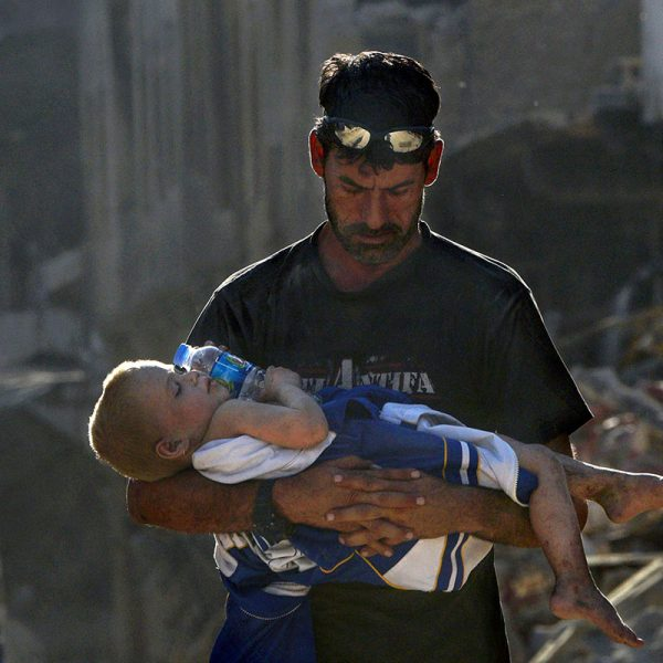 A doctor walks through a warzone carrying an injured baby