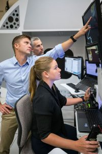 USD alumnus Matthew Dominick points at a computer screen while training to be an astronaut.