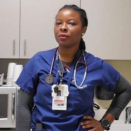 USD alumna nn Lawani '18 (MSN), a COVID nurse, with hand on hip in scrubs